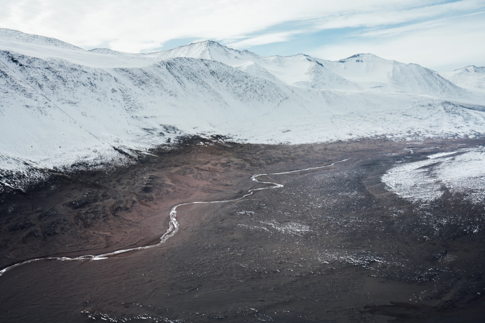 an ariel shot of a winding stream in a valley between snowcapped mountains