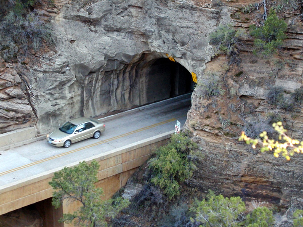 a car on a bridge, about to enter a tunnel on the side of the mountain