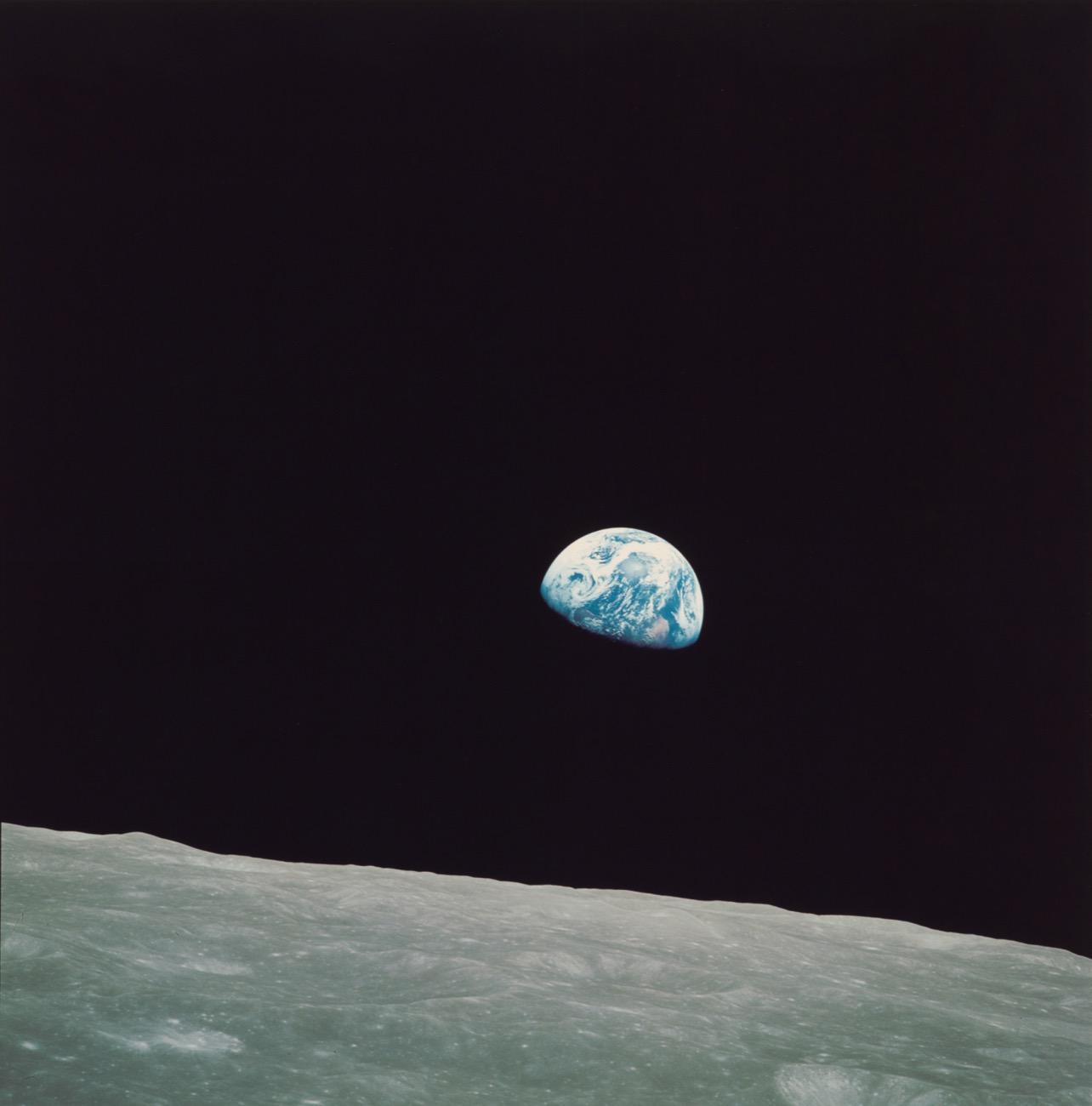 the curve of the moon in the foreground with the earth, half in shadow, sitting in the blackness of space