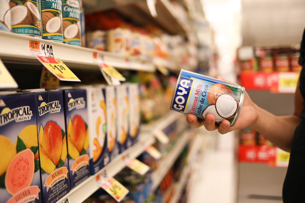 a person at the grocery store holds a can of coconut milk