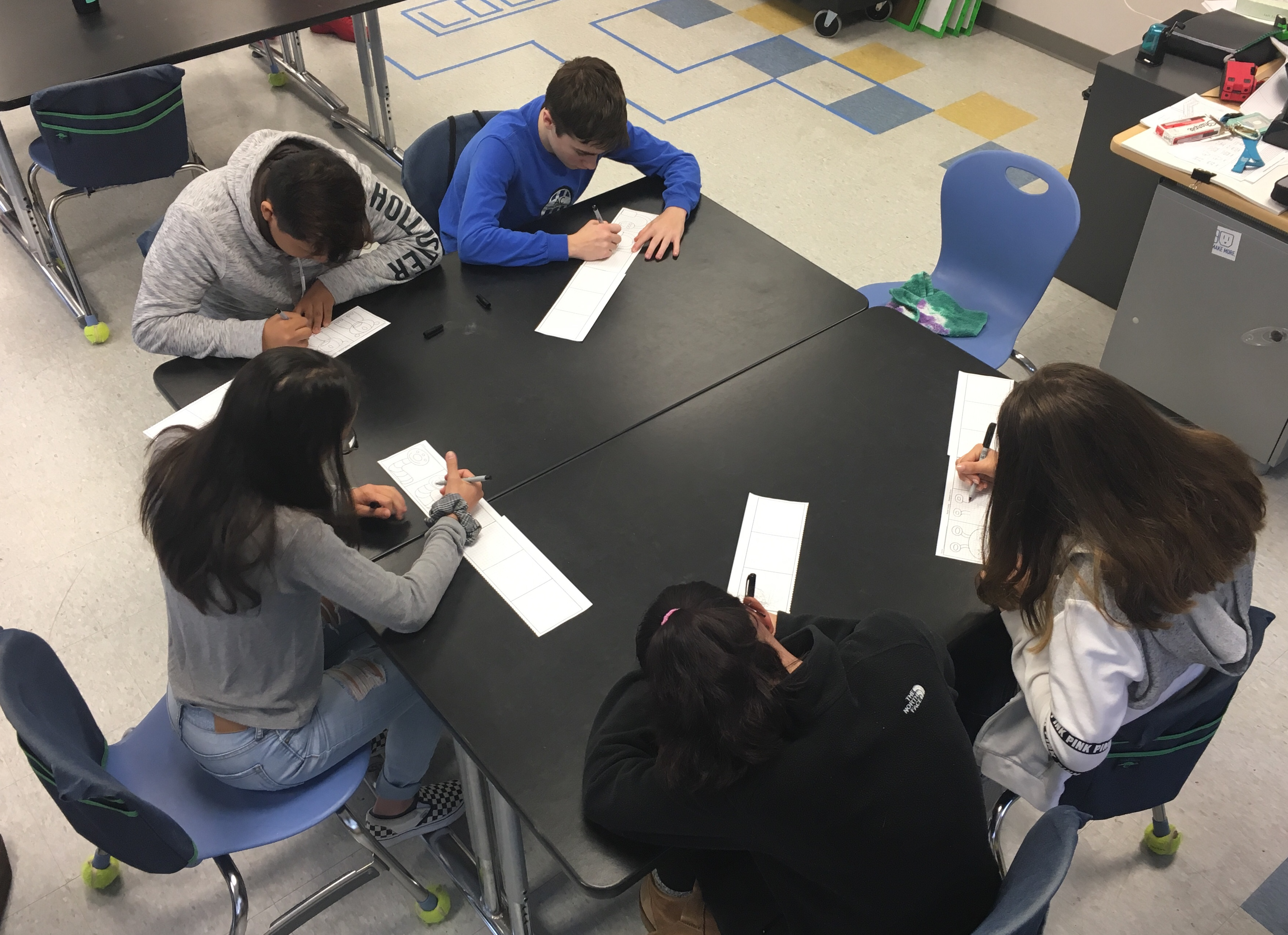 five students working on the activity, sitting around a table