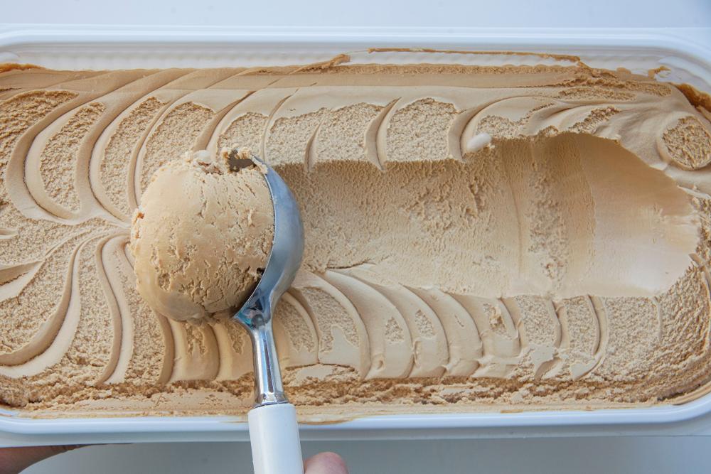 tan-colored ice cream. an ice cream scooper scoops a big helping of the ice cream
