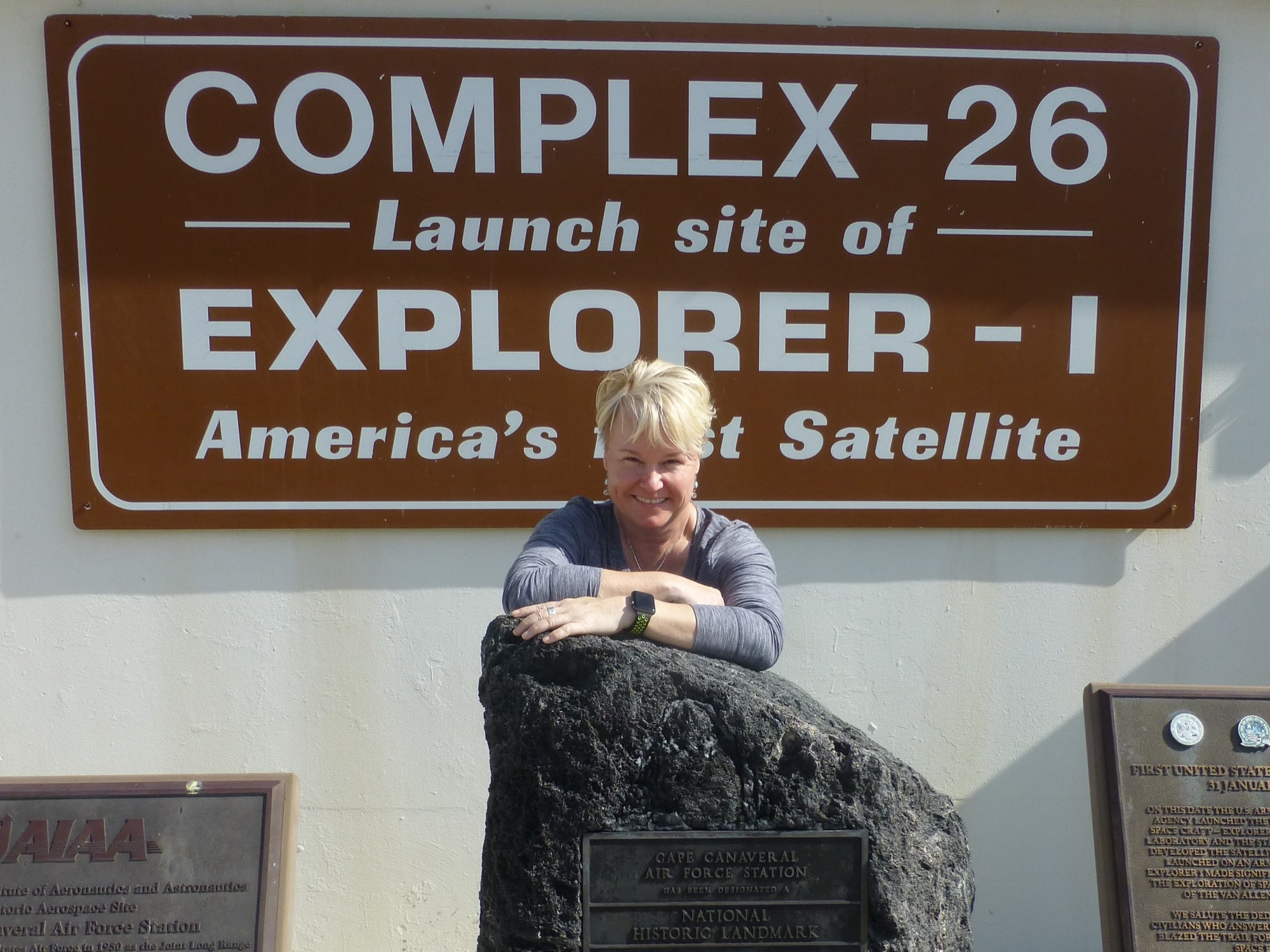 a woman stands in front of a sign that says 'complex-26 launch site of explorer - I America's first satellite