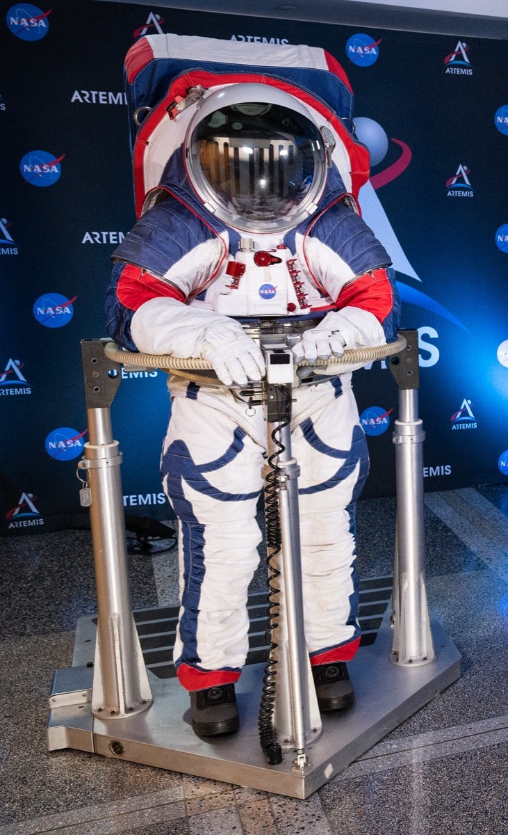 a full body shot of a space suit that is color red, blue, and white. on the back is a large pack