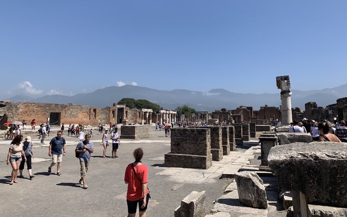 city ruins filled with meandering tourists under the summer sun. in the distance are mountain ranges