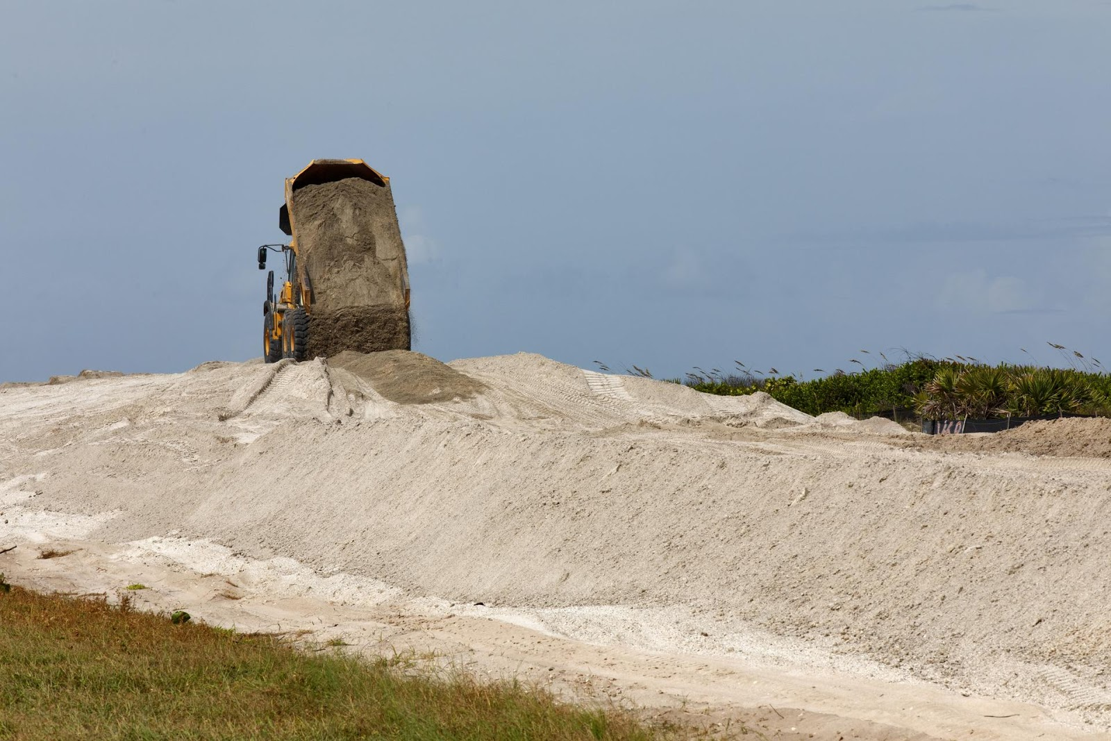 a dump truck on top of a large sand dune dumping more sand onto it
