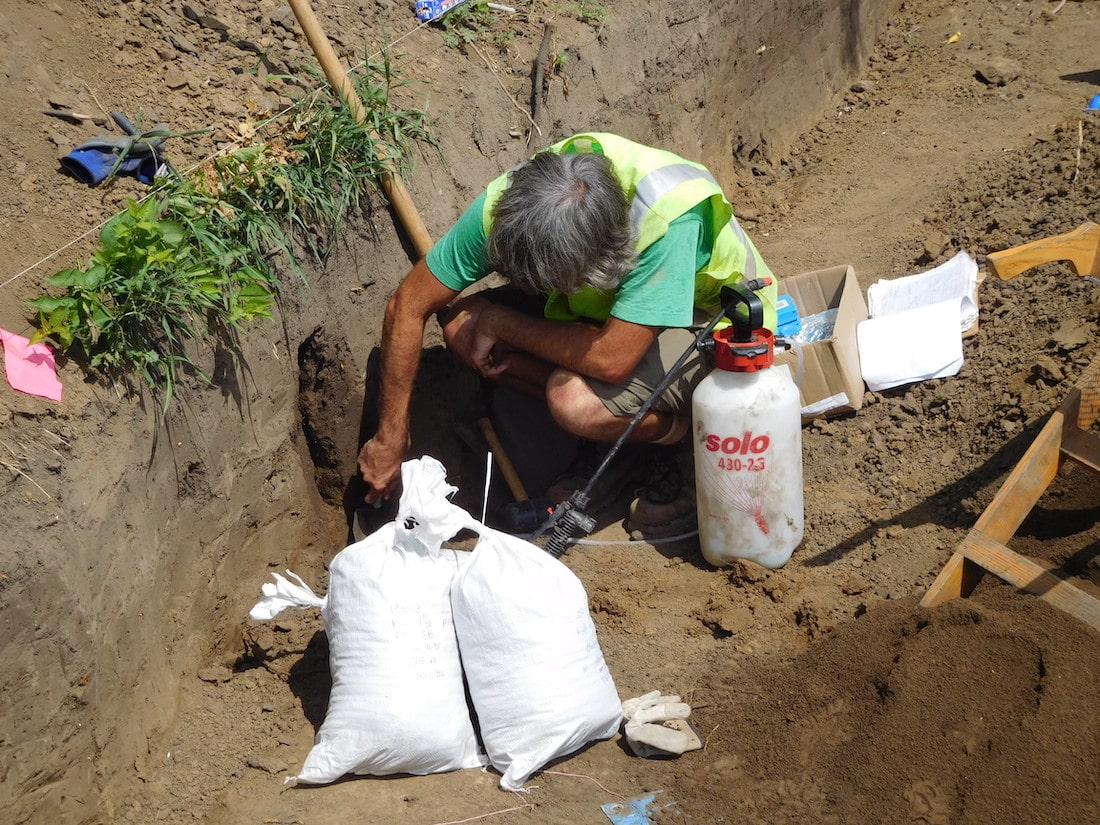 an archaeologist wearing a green vest bends over two medium-sized bags stuff with soil in a dirt trench