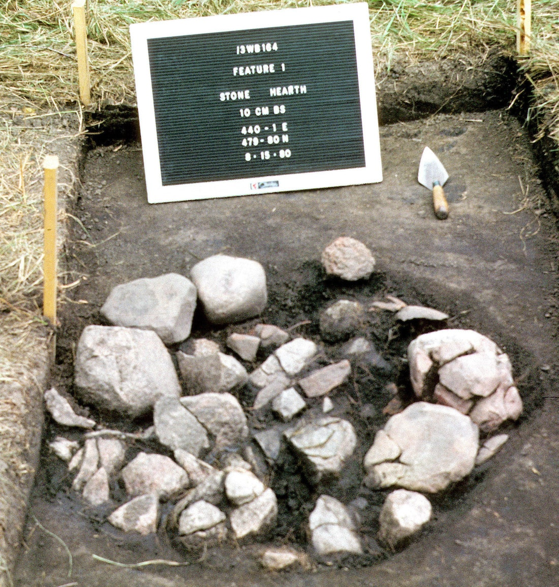 whitish and gray stones piled in a circle in a depressed hole with a sign explaining that they are a former stone cooking pit.