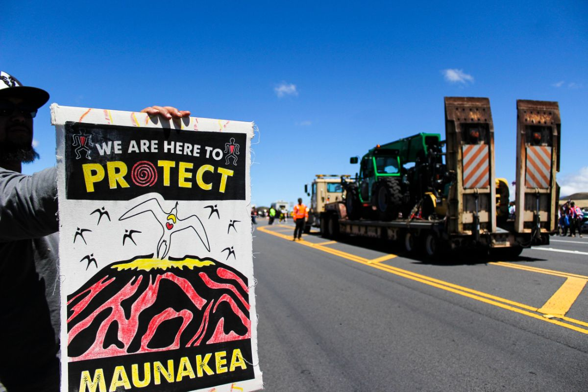a protester/protector holds a sign that reads 'we are here to protect mauna kea.' in the background is a large tractor and construction truck
