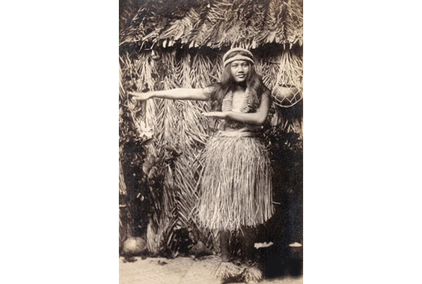 a black white photo of a woman in a grass skirt with her arms held out across her body traditionally hula dancing