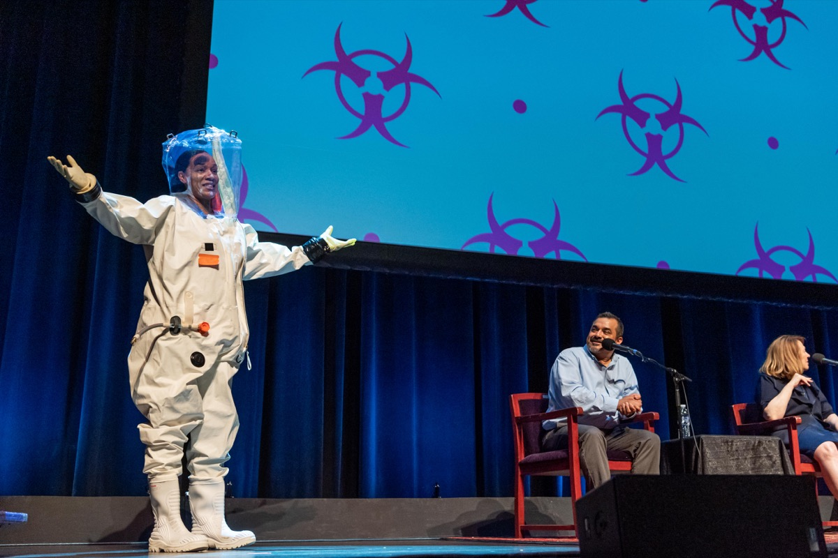 a woman stands on stage in an astronaut like suit. next to her sit two scientists with mics, talking to ira flatow