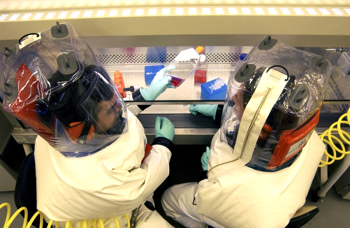 an overhead look at two scientists in puffy safety suits working with some vials