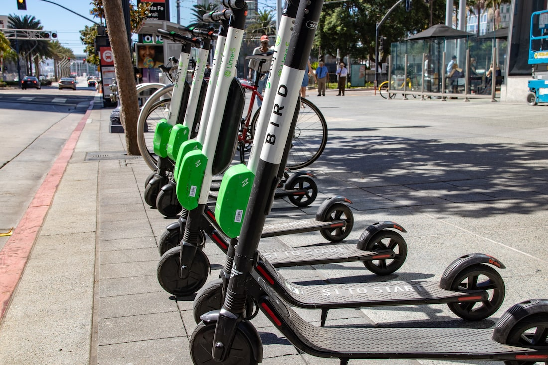 a row of green and black electric scooters with large wheels lined up on a grey sidewalk next to the street