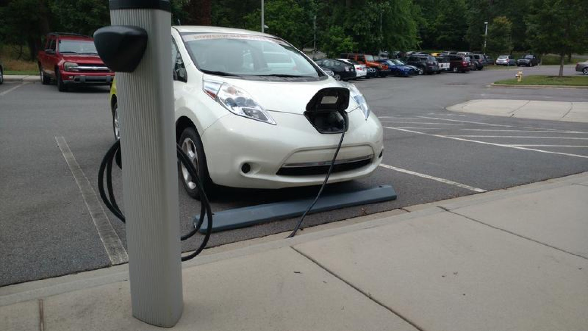 a white electric car is charging on a pump