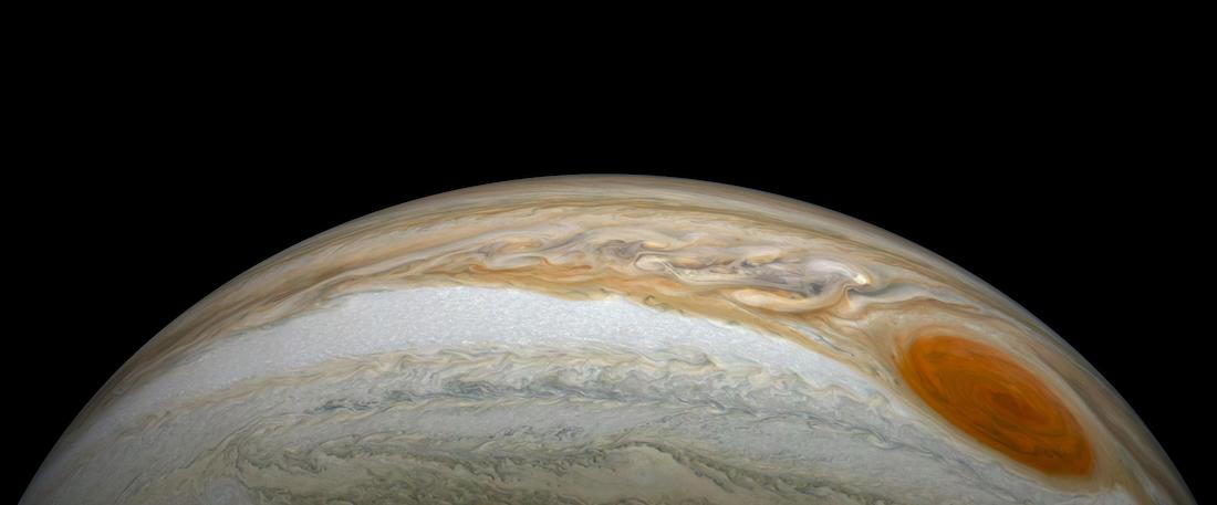 panoramic view of the swirls on jupiter with the great red spot, against a black background
