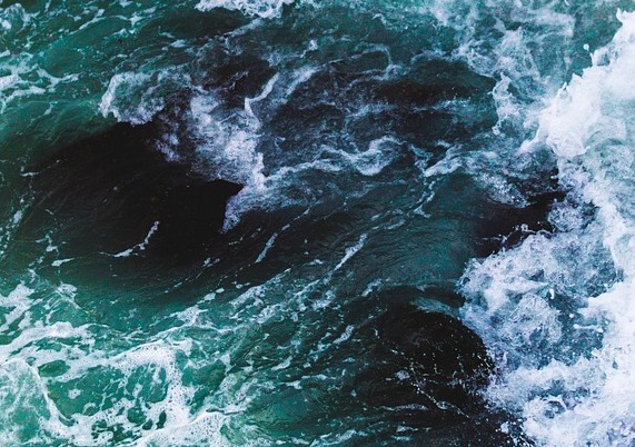 close up shot of blue-ish, green-ish, black-ish ocean waves with some white foam emerging from the choppy water