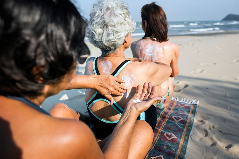 three women sitting lined up putting sunscreen on each other's backs