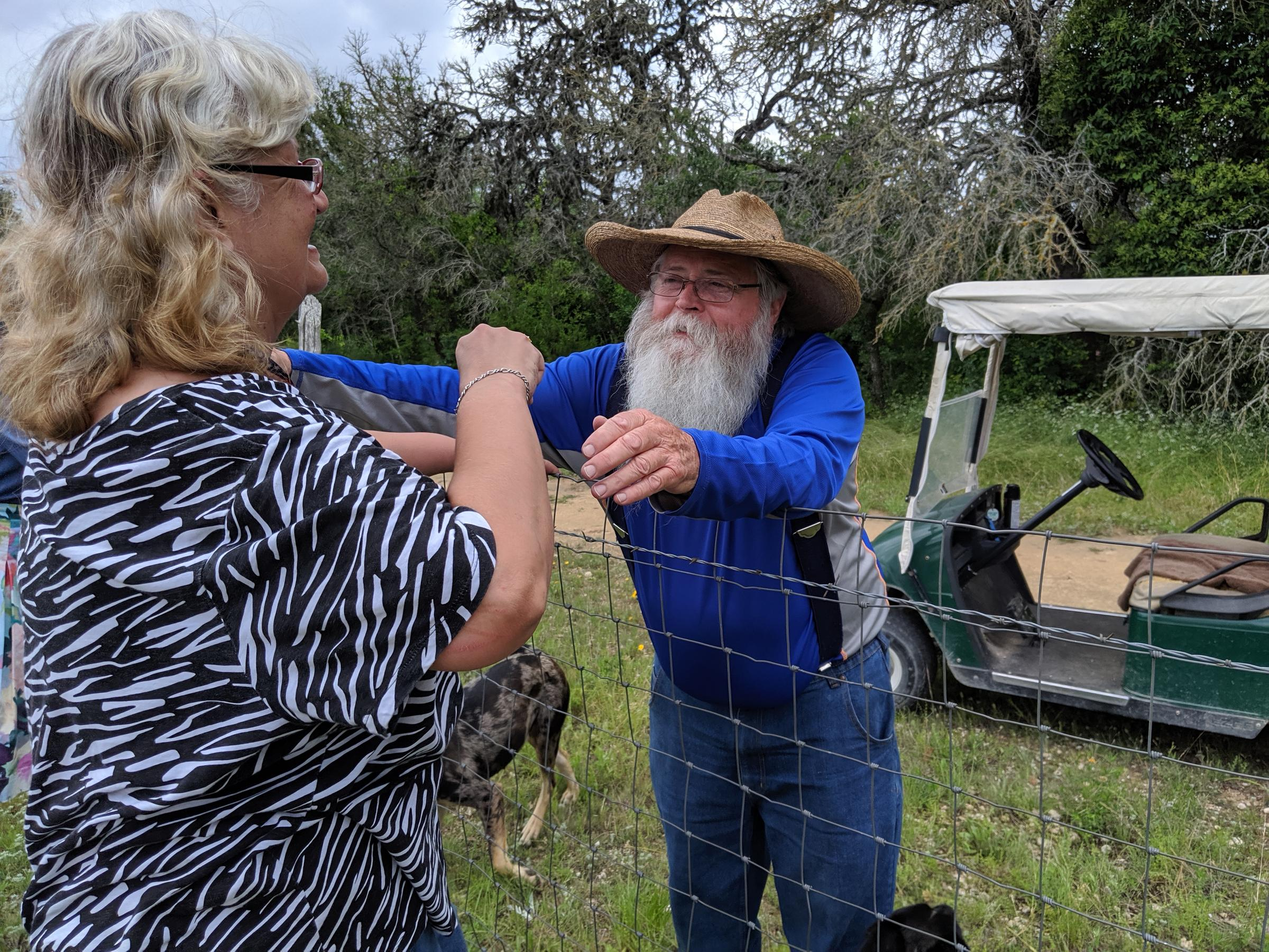 man with big white beard and giant hat leans to hug a woman over a wire fence