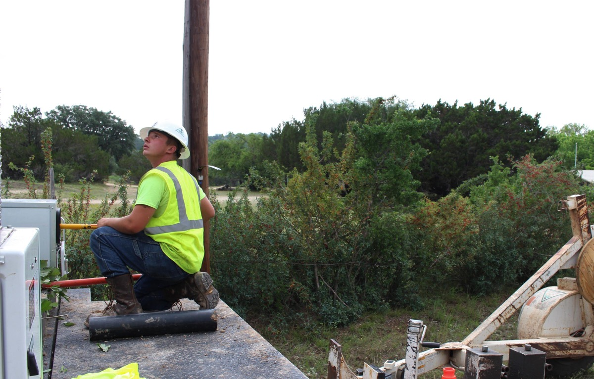 a man in a construction uniform looking up at the sky on the side of a road in rural texas