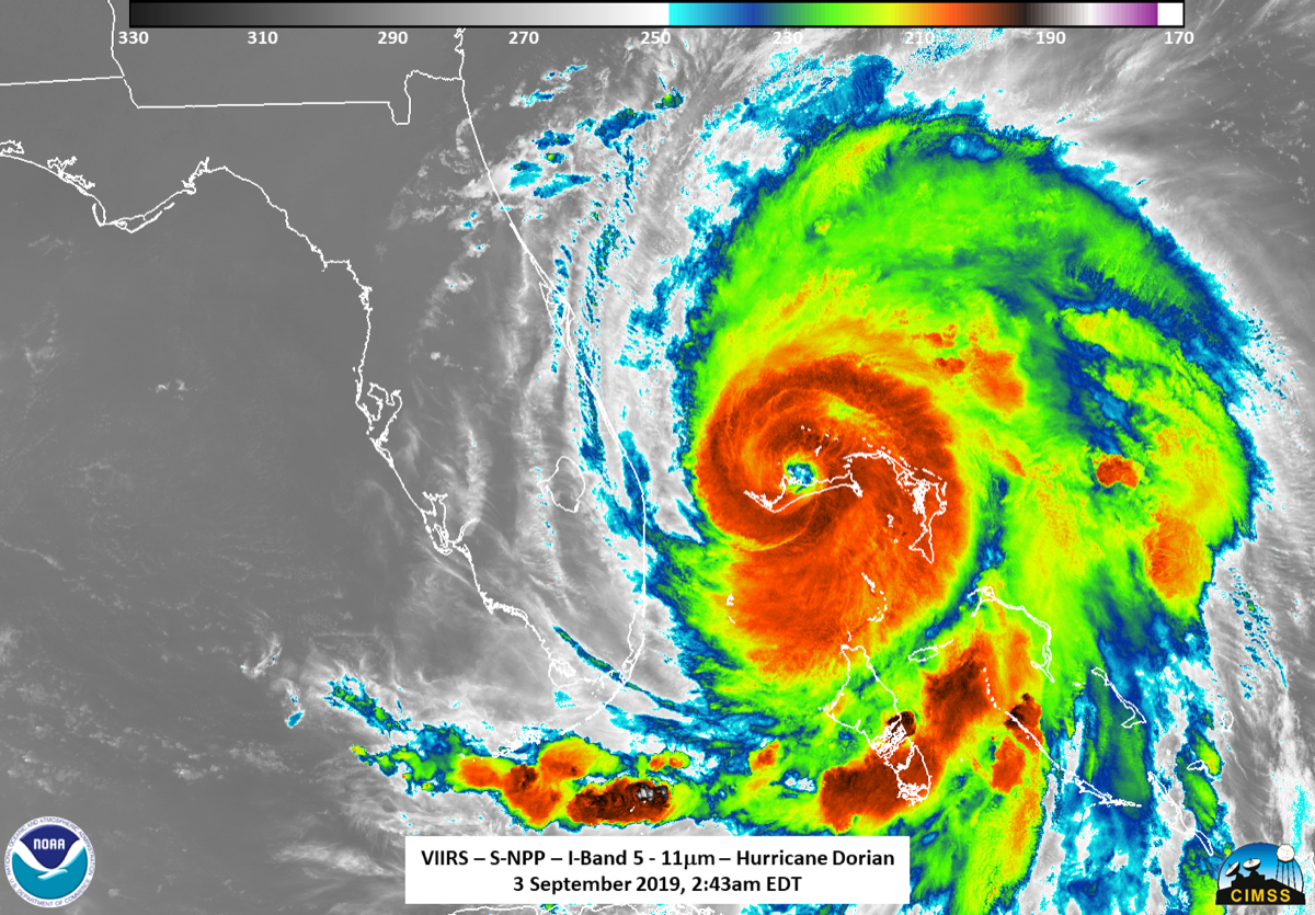 a satellite image of a hurricane over the Bahamas nearing the coast of florida. its center is a dark orange red, indicating its intensity