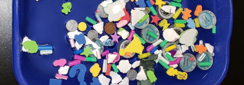 Plastic bin with water and piece of plastic to simulate the Great Pacific Garbage Patch