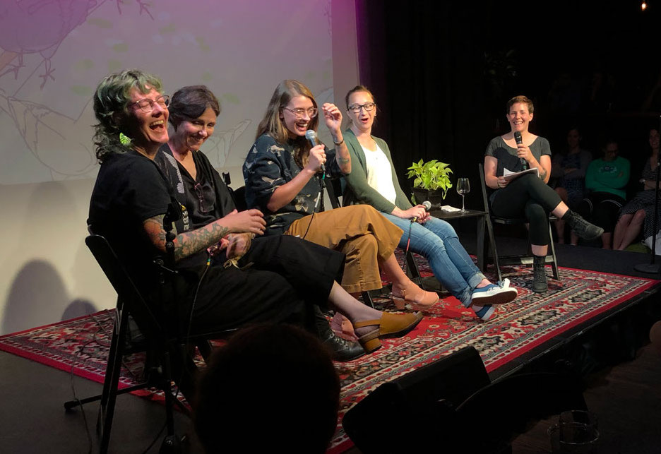 five women stage all with mics laughing with an illustrated bird background behind them