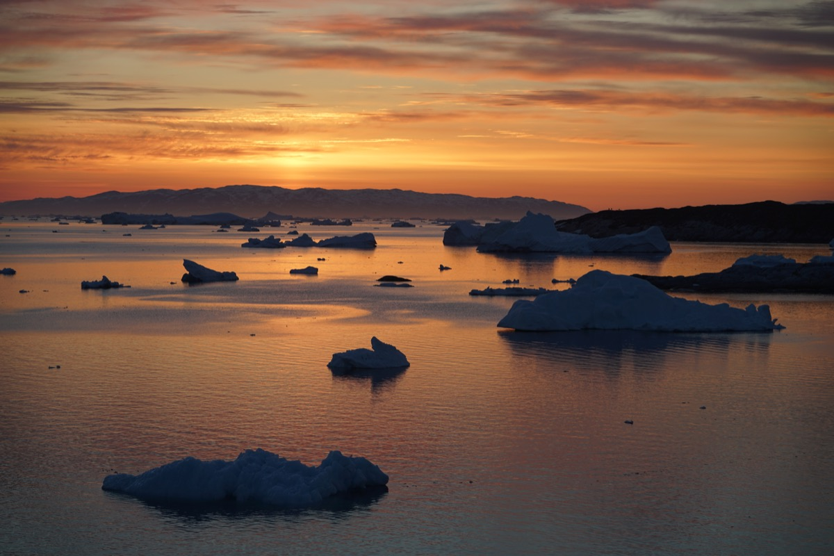 a sparse collection of icebergs underneath an orange sky