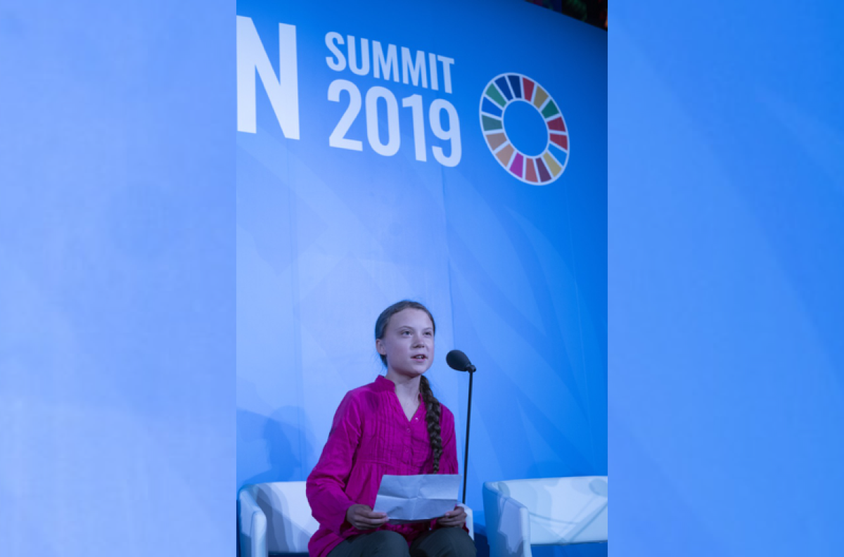 young girl with long braid wearing a reddish-pink shirt sits in front of a microphone giving a speech, with UN Climate branding in the background