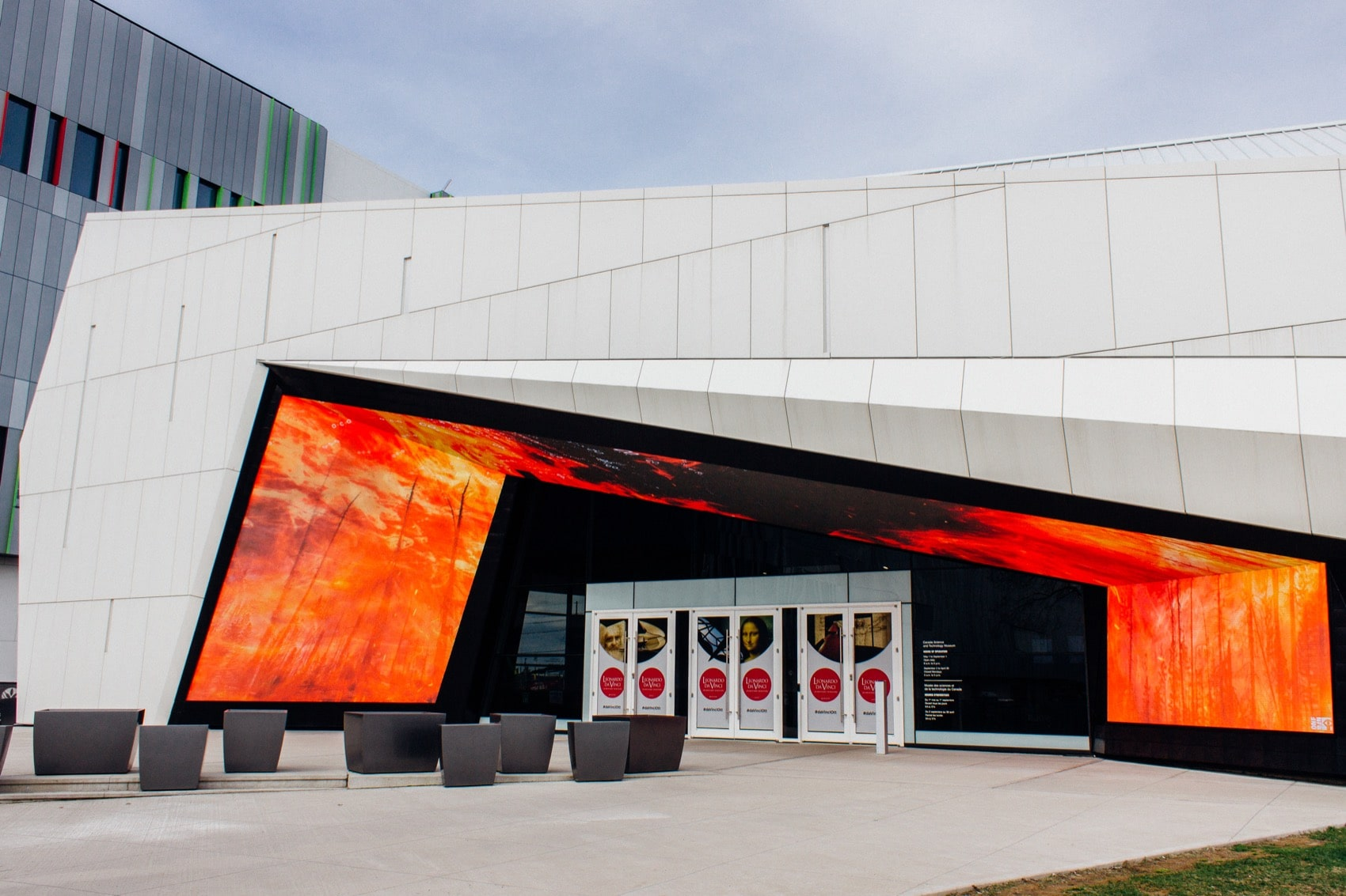 the exterior of a science museum, which is white and futuristic looking with a large video display that frames the doorway