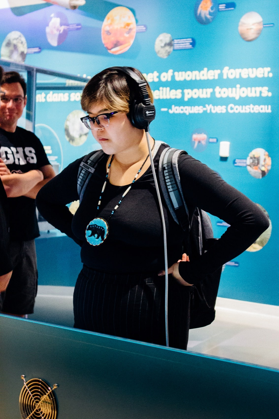 a student at a museum with headphones on listening to an exhibit