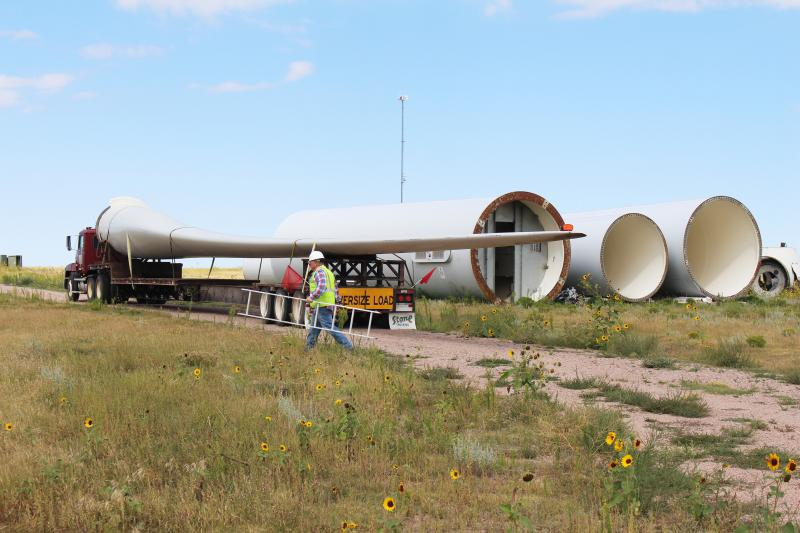 four giant wind turbine blades lay on their side on the ground