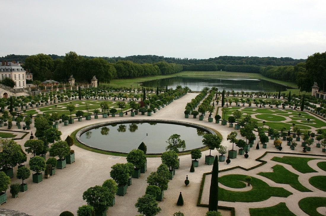 an aerieal view of a circular pond with rows of straight, geometrically aligned trees and trimmed hedges