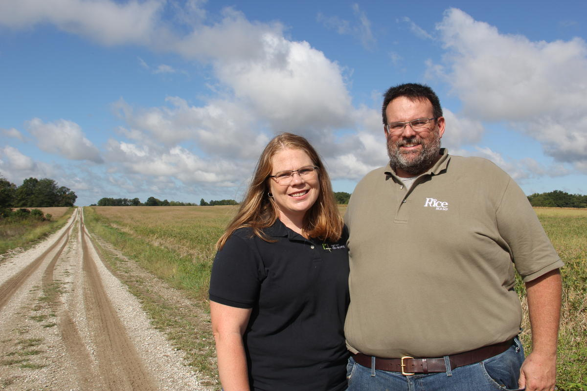 Couple stands in front of their farm