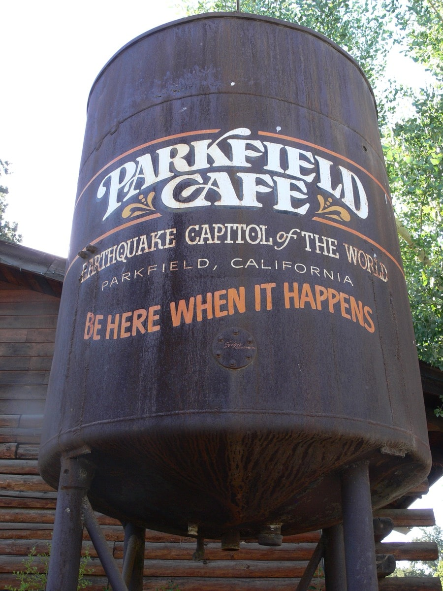 a water tower that says 'parkfield cafe, earthquake capitol of the world, be here when it happens'