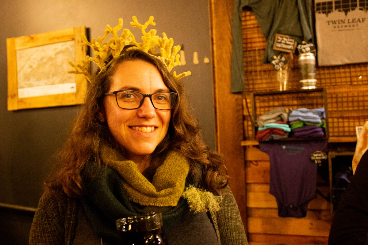 a woman wearing a crown made of brown pipecleaners than resemble a lichen