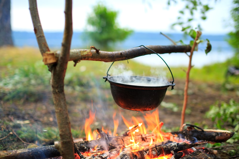 a pot hanging over a fire outside, suspended by a stick contraption