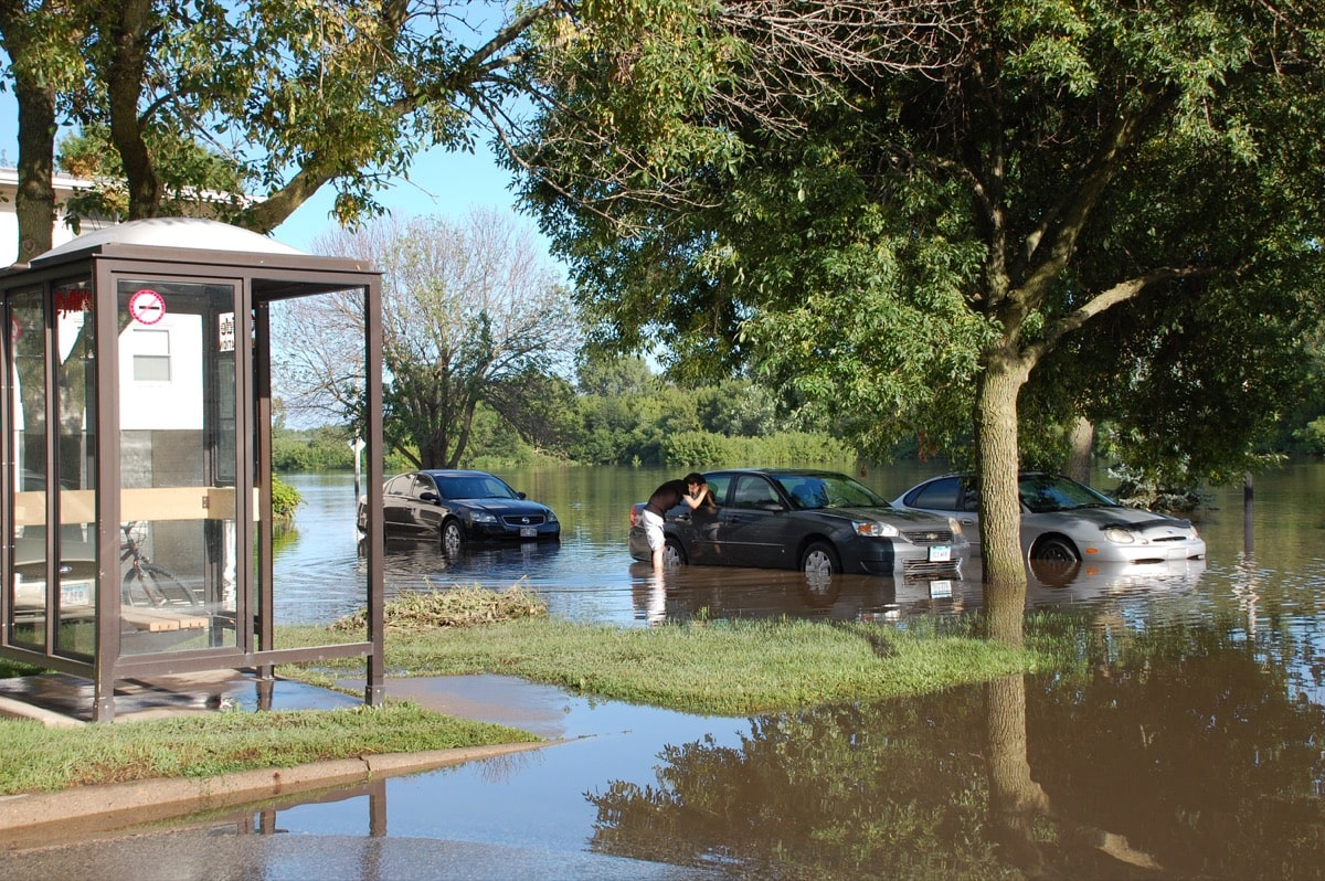 a person looks into a car in a flooded parking lot