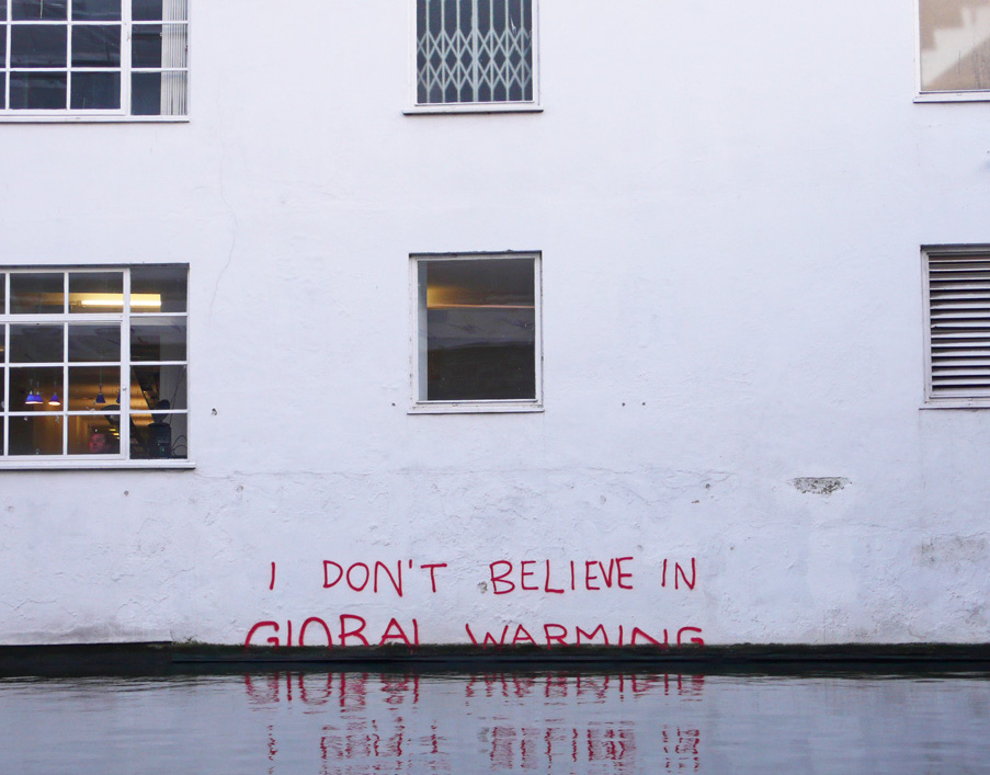 "water reaching up high to the edge of a building. right at the edge of the building where the water meets the building are the words in red graffiti ""i don't believe in global warming."" the words appear to be slipping beneath the water line"