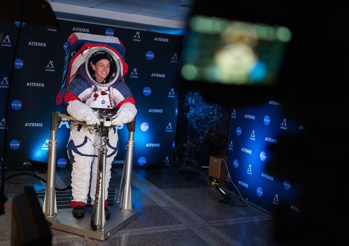 a woman astronaut stands in a new space suit