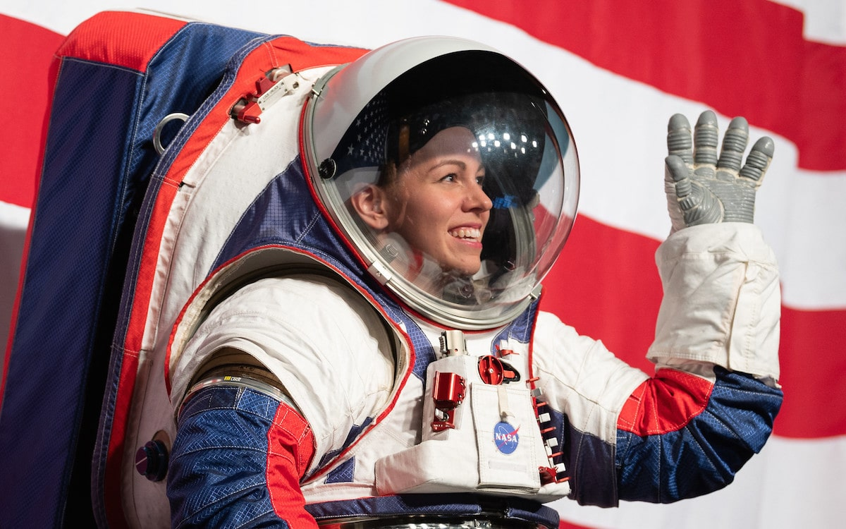 a woman astronaut in a space suit waving