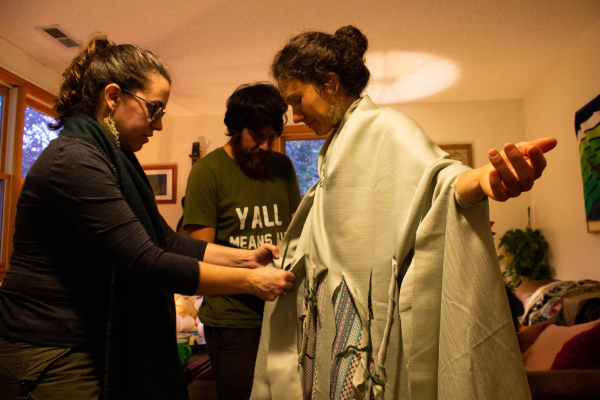 two people assist a woman creating a costume by tying strips of green table cloth