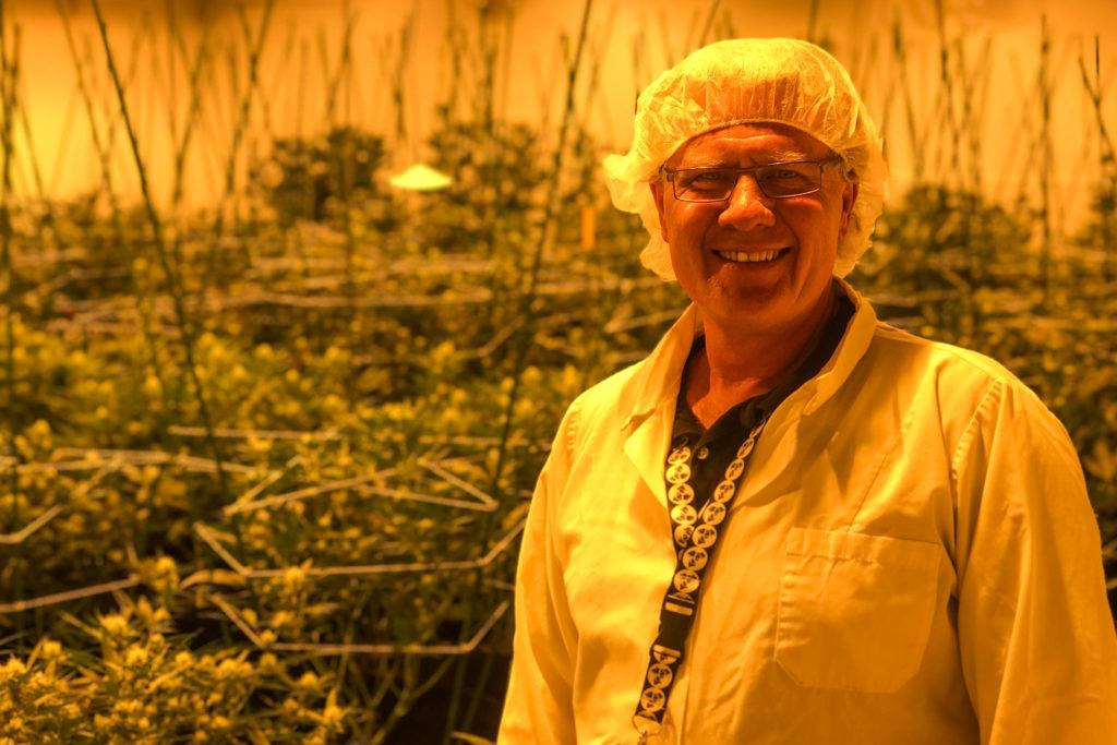 man in labcoat smiling at camera in marijuana farm lab