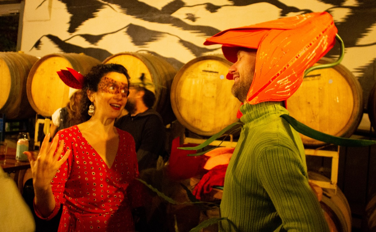 two people chat animatedly at a bar dressed up as two flowers