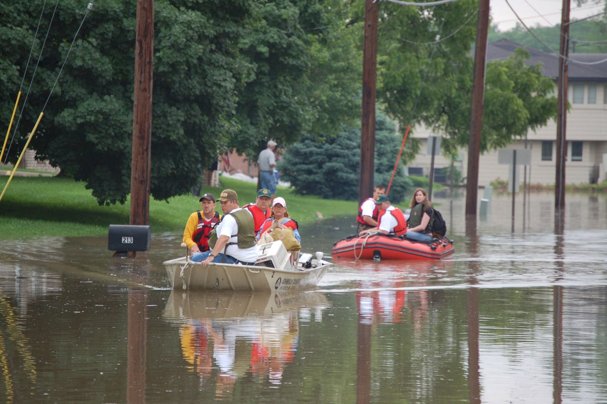 people on rescue boats going down a flooded street