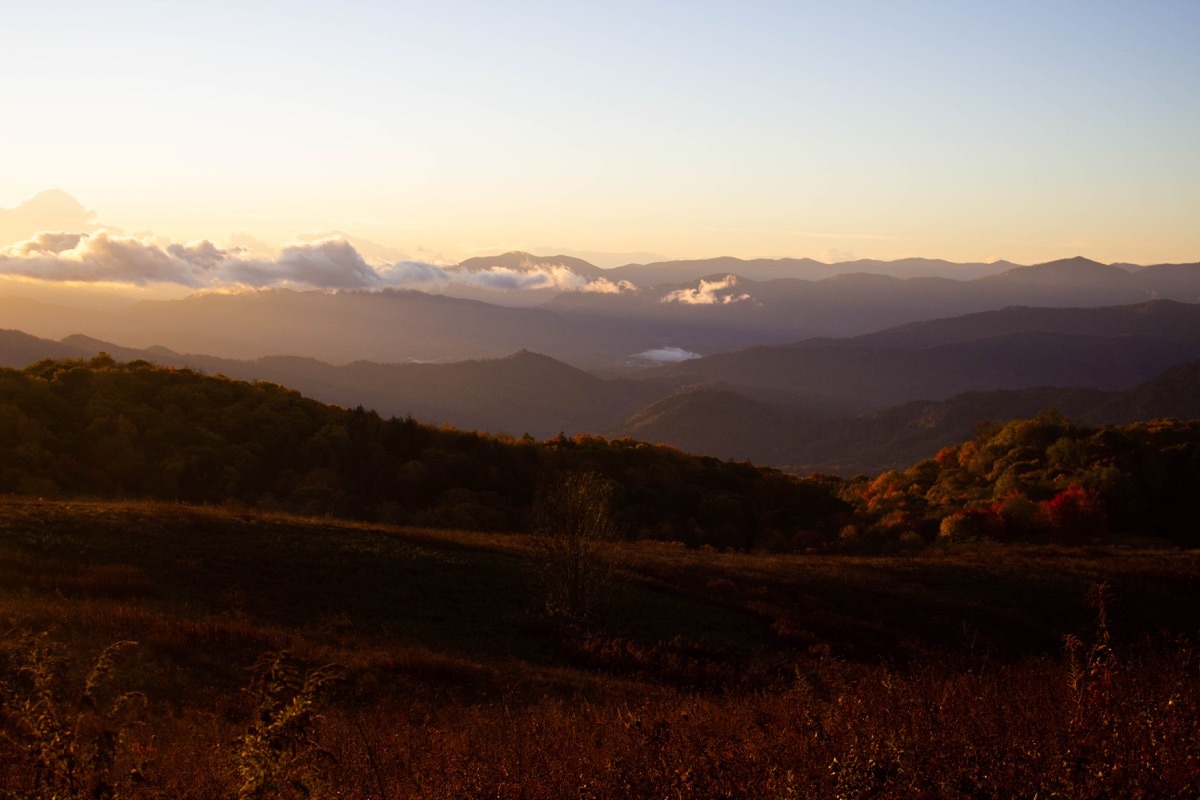 sun rise over folds of mountains, making them glow red with the autumn leaves