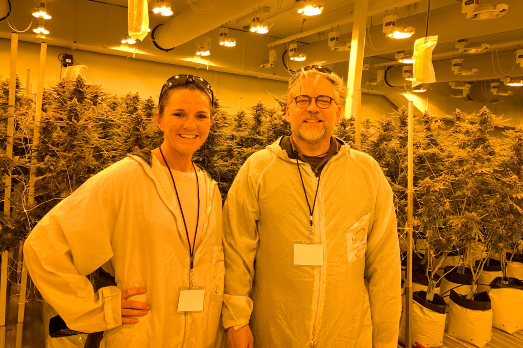 two people in labcoats smiling at camera in marijuana farm lab