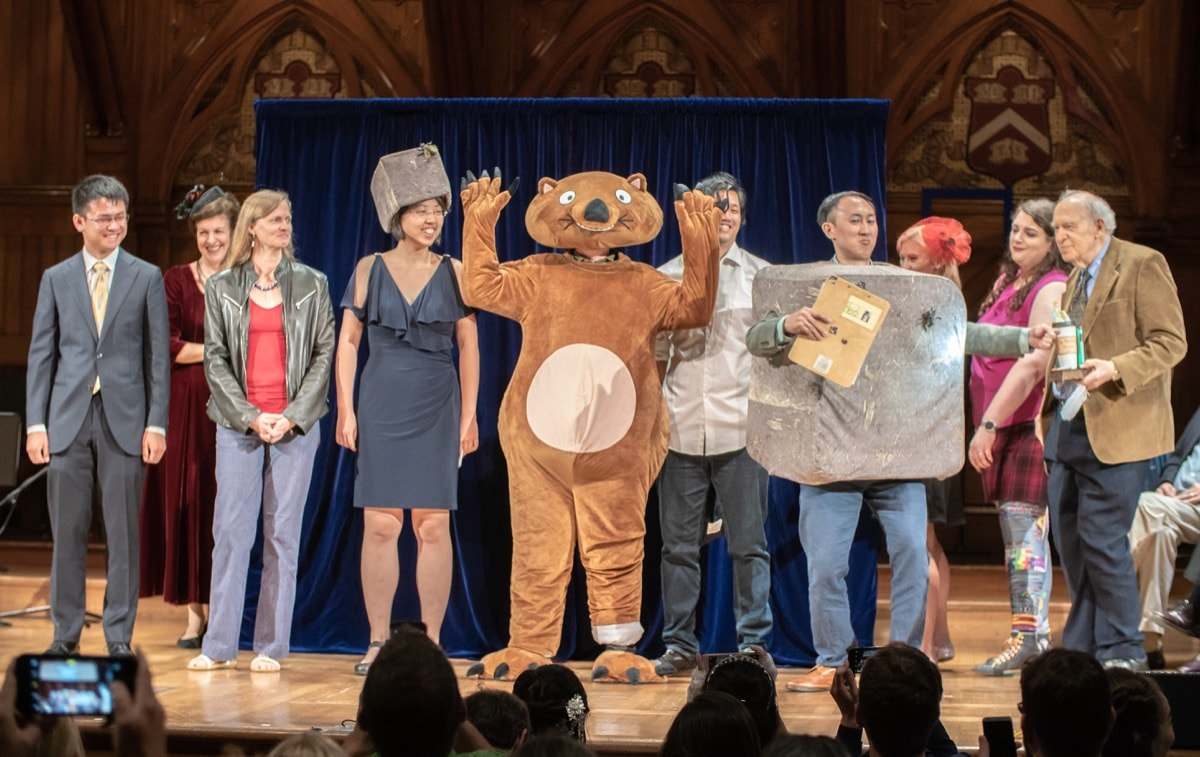 a group of scientists on stage, one is dressed as a wombat and another is dressed up as a cubed wombat poop
