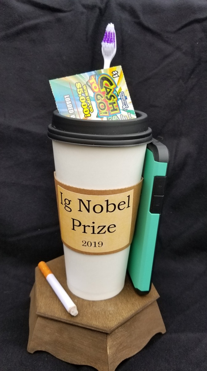 a coffee mug with a tooth brush, a cellphone case, a lotto ticket, and a used cigarette constructed as a trophy