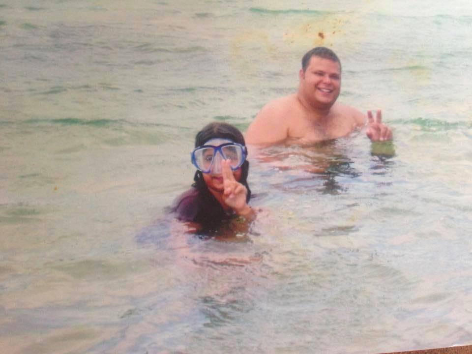 A girl and a man in the water on a beach