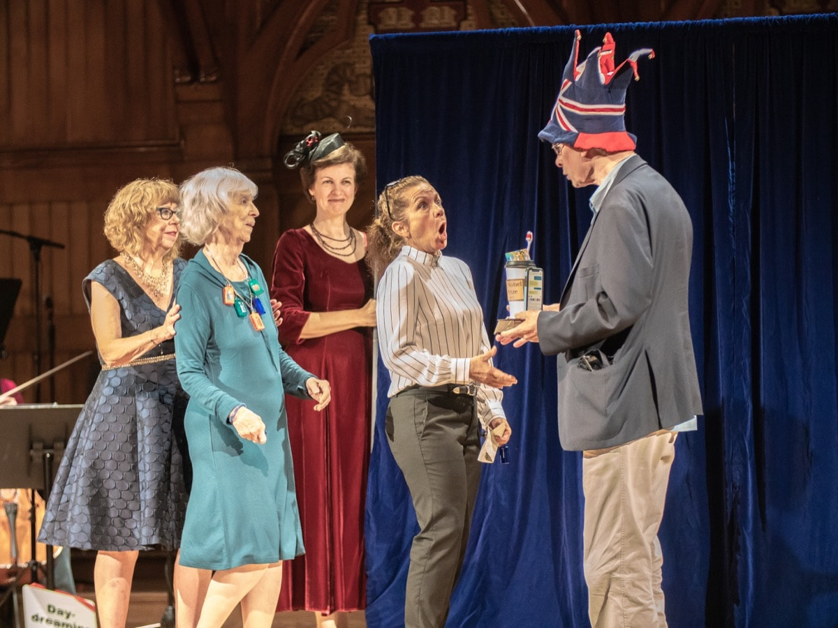 four women scientists on stage receiving an award from a man in a tall hat with england's flag on it